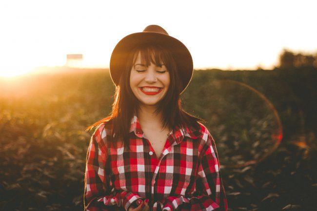 Zufriedene, lachende Frau mit Sonnenuntergang im Hintergrund