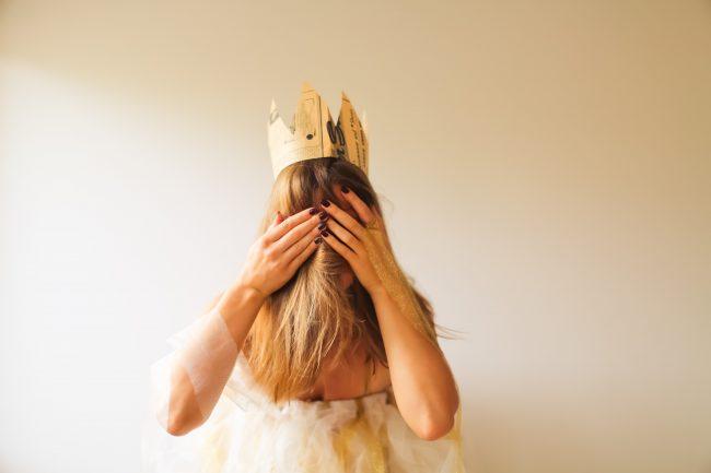Frau mit einer Krone auf dem Kopf, die ihr Gesicht hinter den Händen versteckt