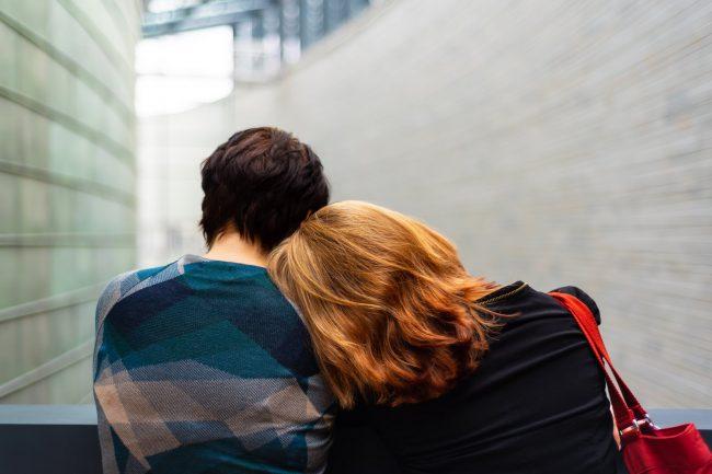 Ein Liebespaar sitzt auf der Bank. Der Kopf der Frau liegt auf der Schulter des Mannes
