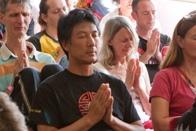 Menschen, die mit geschlossenen Augen meditieren