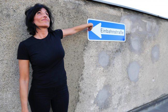 Monika Mazur neben einem Straßenzeichen Einbahnstraße